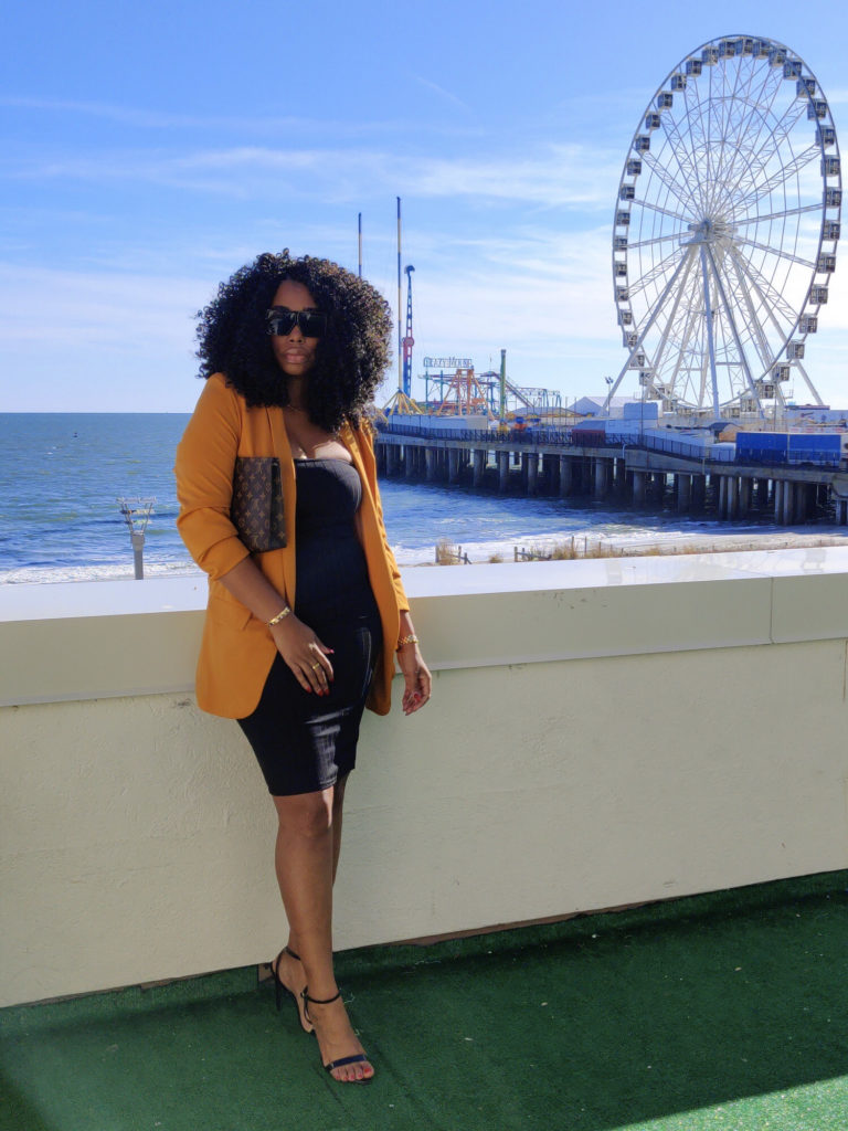Beautiful black woman in front of Ferris wheel